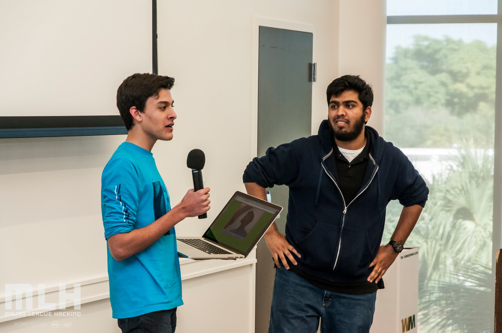 two male students, one holding a laptop and a microphone, presenting their project to the audience