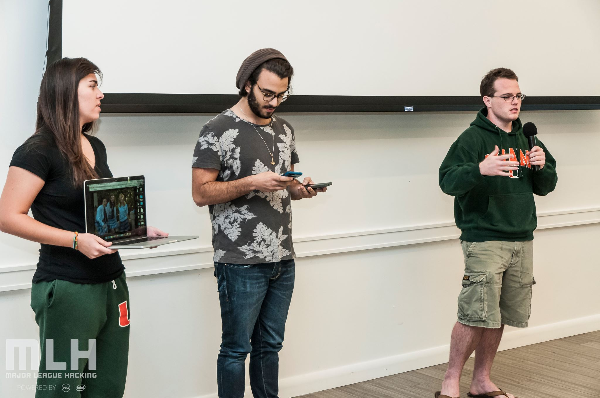 three college students standing and presenting a project