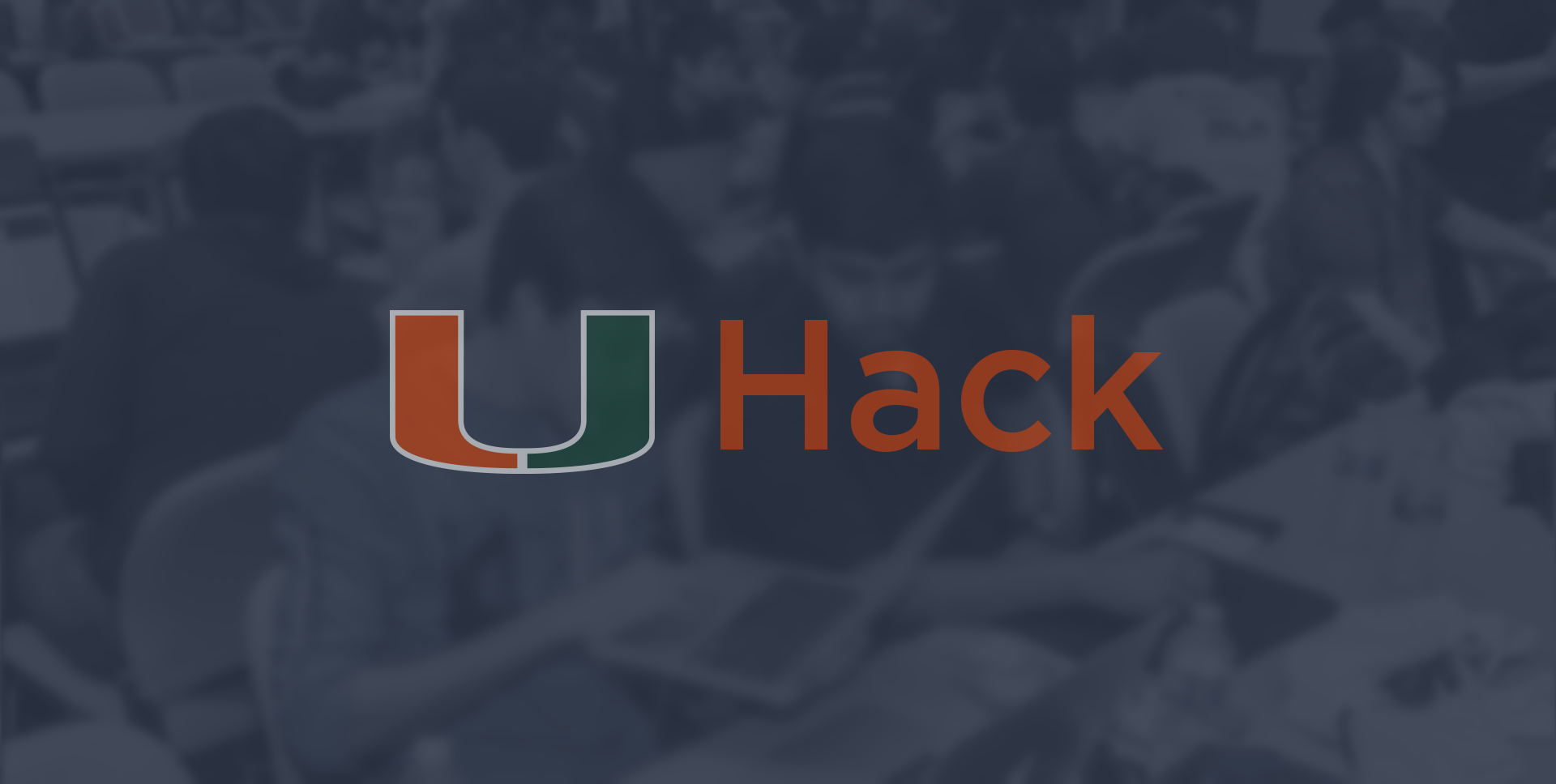 Blurred photograph of two male students working at a hackathon with the writing 'U Hack' in the foreground