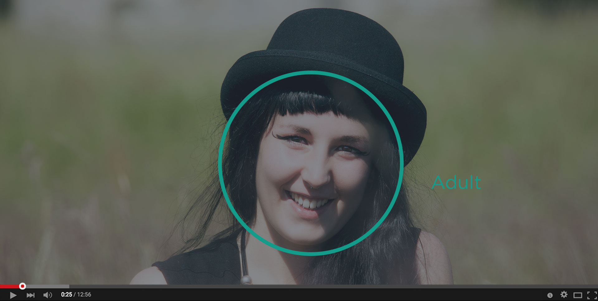Screenshot of a media player showing the headshot of an adult female with a face detection frame overlayed and a text that reads 'Adult'.